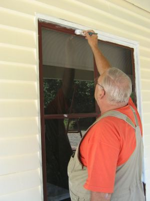 Dad painting a front window at Sewjourn in Lancefield