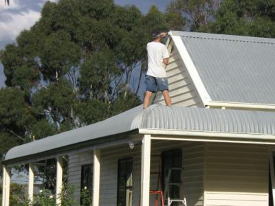 Mal painting the roof at Sewjourn in Lancefield